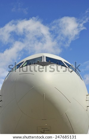 Front view of an airplane with blue sky - stock photo