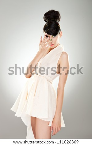 Front view of an alluring young woman with fancy make-up and nails, wearing a fashion white dress. She is holding her hand over her face - stock photo