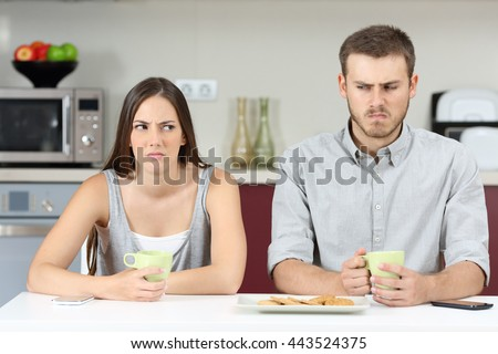 Front view of an angry couple looking each other sideways after argument in the kitchen during breakfast at home - stock photo