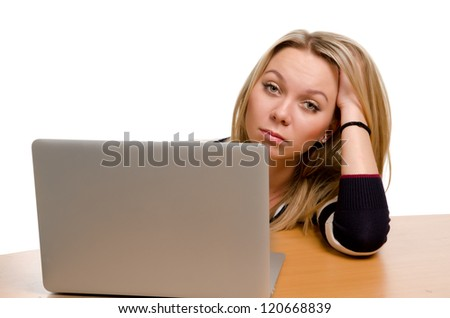 Front view of an attractive bored young woman sitting behind her laptop with her head resting on her hand - stock photo