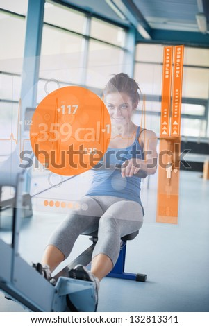 Front view of an attractive girl on rowing machine with futuristic interface showing calories - stock photo