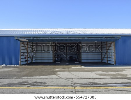 front view of an empty aircraft hangar with open doors
