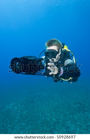 Front view of an Underwater camerman filming in crystal clear water. MORE INFO: Model released