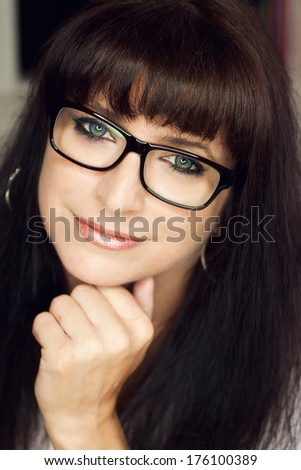 Front view of attractive brunette woman with glasses - stock photo