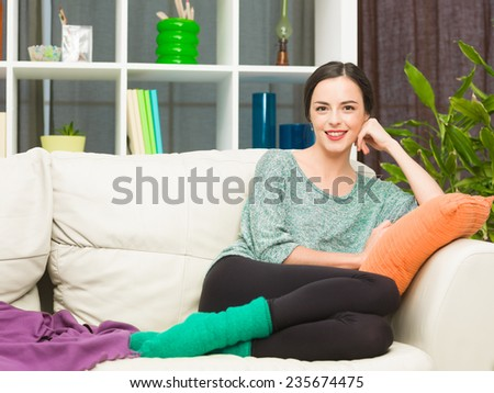 front view of beautiful young woman sitting on cosy sofa at home and smiling - stock photo