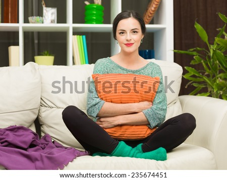front view of beautiful young woman sitting on cosy sofa at home, hugging a pillow and smiling - stock photo
