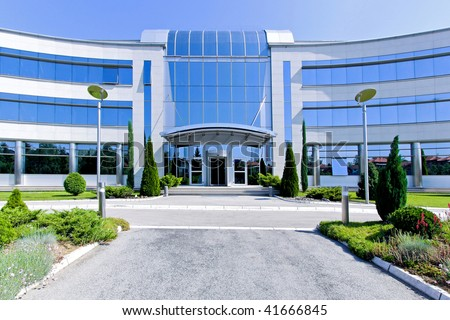 Front view of blue glass office building - stock photo