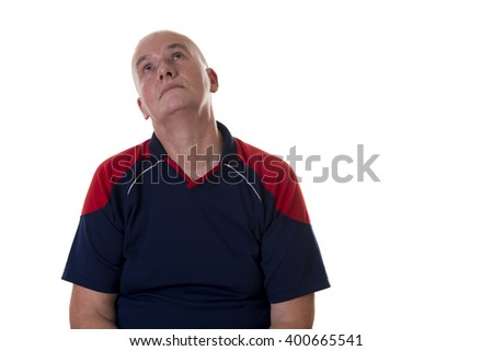 Front view of bored older man in blue and red short sleeve shirt looking up over white background