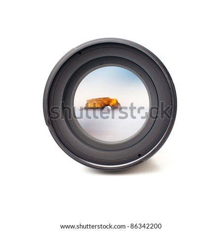 Front view of camera lens with ocean and mountain landscape image reflection - stock photo