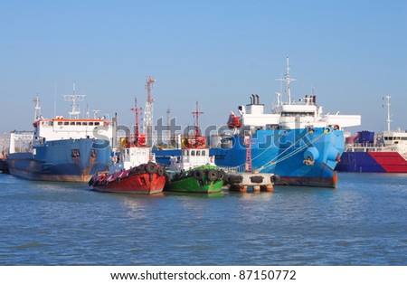 Front view of cargo ships and guard boats docked in port - stock photo