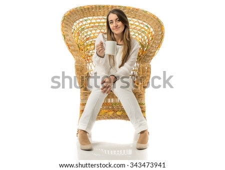 Front view of caucasian woman offering cup of coffee over wicker chair, white cup of coffee for texts - stock photo