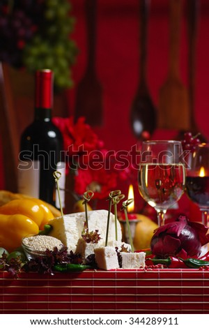 front view of cheese delicatesses, onions and peppers, a bottle and two glasses of wine, in a warm atmosphere, with red background and tablesetting - stock photo