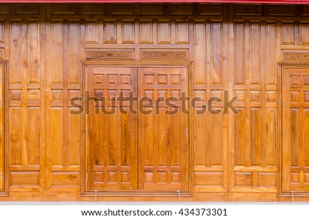 front view of closed wooden window on a wooden wall. - stock photo