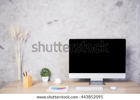 Front view of creative designer desktop with blank computer monitor, coffee cup, colorful diagram, keyboard, stationery items and plant on concrete wall background. Mock up - stock photo