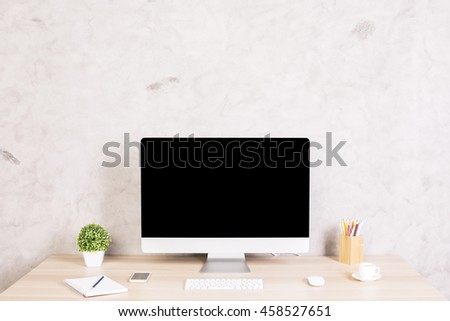 Front view of creative designer desktop with blank computer monitor, coffee cup, smartphone, keyboard, stationery items and plant on concrete wall background. Mock up - stock photo