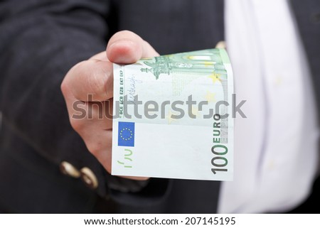 front view of 100 euro banknote in businessman hand close up - stock photo