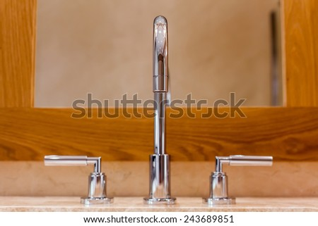 Front view of Faucet and marble sink in the luxury hotel - stock photo