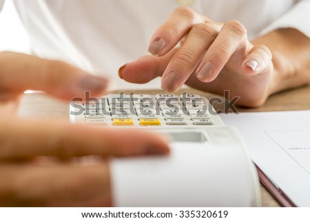 Front view of female banker calculating expenses and income using adding machine while checking a printout receipt. - stock photo