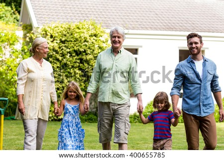 Front view of happy family walking outside house at yard - stock photo