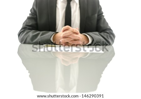 Front view of insurance agent sitting at his desk with papers and documents ready for his clients to sign them. Focus on a pen. - stock photo