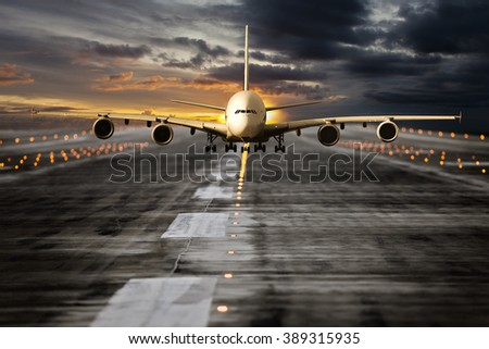 Front view of large passenger airplane. Aircraft runs along the airport runway during sunset time.