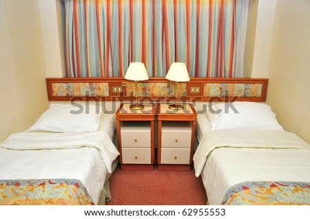 Front view of luxurious resort room with twin beds, in a cruise ship cabin. - stock photo