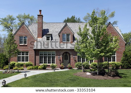 Front view of luxury home with cedar shake roof - stock photo