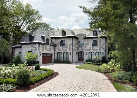 Front view of luxury home with circular driveway - stock photo