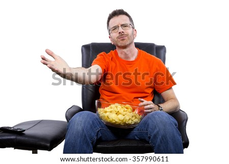 Front view of man watching TV while eating potato chips - stock photo