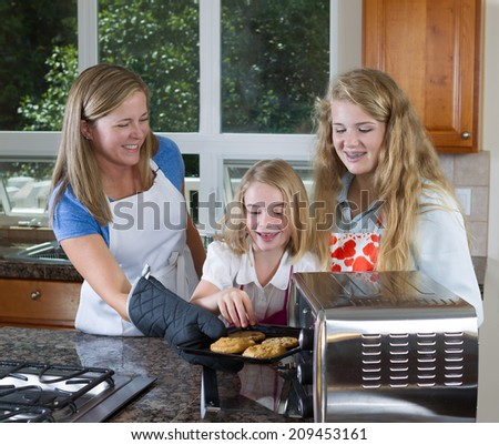 Front view of mother pulling out fresh cookies from the oven with her youngest daughter reaching for them  - stock photo