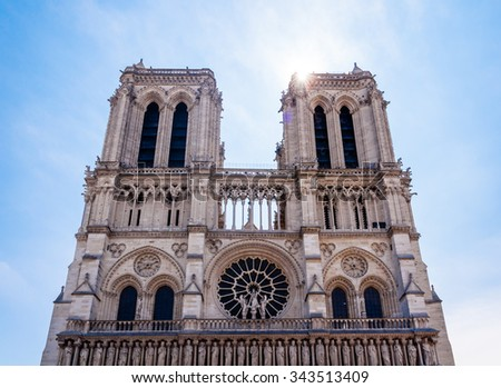 front view of notre dame de paris, france with solar flare - stock photo