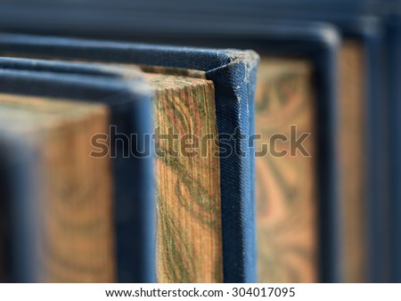 Front view of old books stacked on a shelf