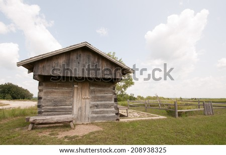 Front view of old pioneer hand-hewn log cabin at Fossil and Prairie Preserve, Rockford, Iowa - stock photo