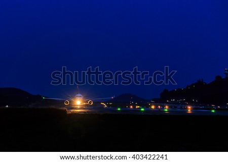Front view of Passenger Airplane at landing strip in the night - stock photo