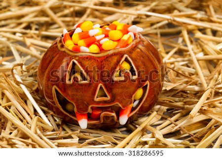 Front view of scary pumpkin with fangs filled with candy corn on straw. Halloween concept. - stock photo