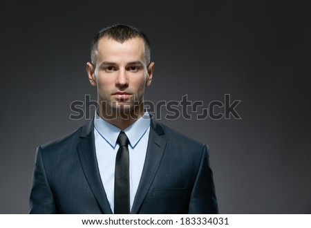 Front view of self-confident businessman in dark suit with black tie. Concept of professionalism and success in business