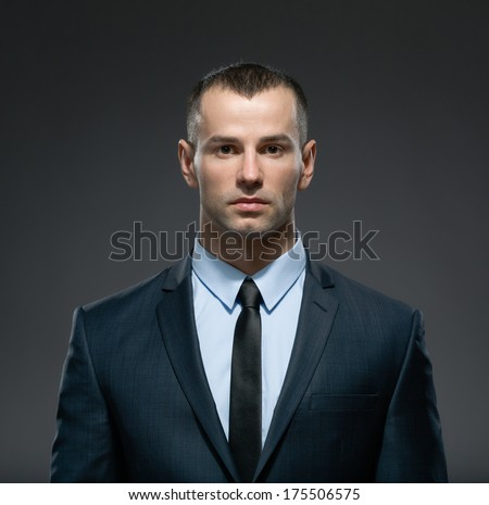 Front view of self-confident businessman in suit with black tie. Concept of professionalism and success in business