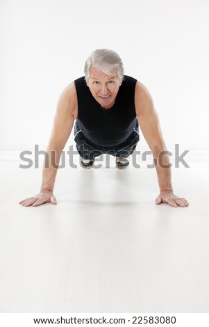 front view of senior man doing push-ups - stock photo