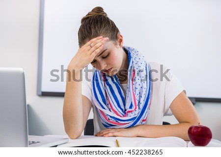Front view of stressed teacher suffering from headache in classroom
