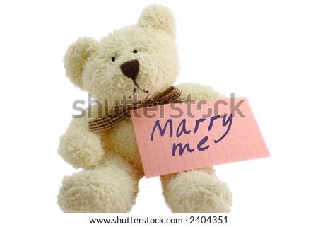 "Front view of teddy bear toy with ""Marry me"" note, isolated on white background - stock photo"