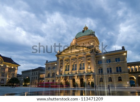 Front view of the Federal Palace of Switzerland (Bundeshaus) on a rainy evening.
