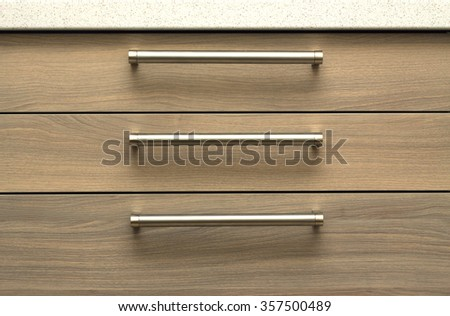 Front view of three closed sliding wooden drawers with metal long handles. Fragment of modern design kitchen furniture, horizontal photo front closeup
