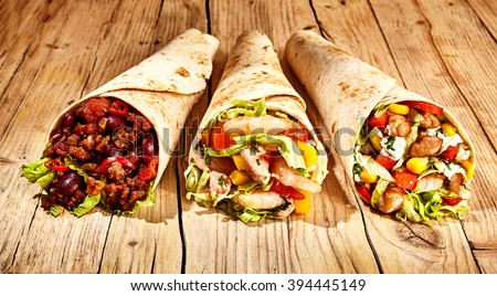 Front view of three delicious Mexican style burritos in wheat tortillas on old wooden table table - stock photo