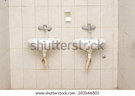 front view of two sinks on a shelf and two modern faucets on the wall