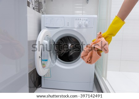 Front view of unidentifiable yellow rubber gloved hand holding dirty pink towel in front of small front loading washing machine