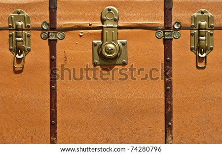 Front view of vintage worn-out  leather suitcase  with three metallic locks in retro style. - stock photo