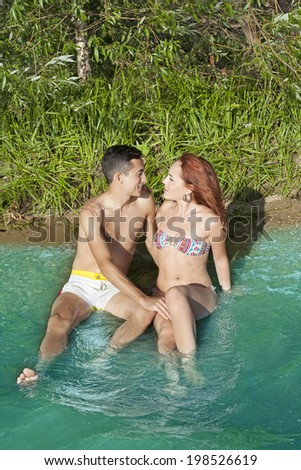 Front view of young adult caucasian embracing couple in love at sand tropical beach background Copy space for inscription Beautiful man and woman sitting in clear blue water with wave