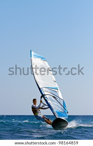 Front view of young man surfing the wind on summer day - stock photo