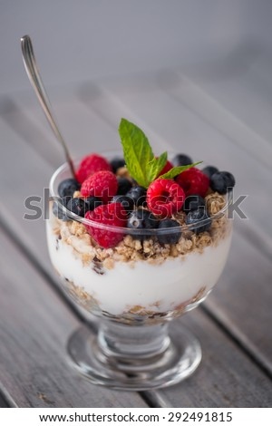 Front view on glass cup full of bluberries, strawberries and raspberriers on wooden table. - stock photo