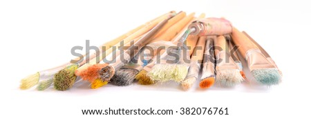 Front view on old used paintbrushes and scraper of an artist (focus on front). Image isolated on white studio background.